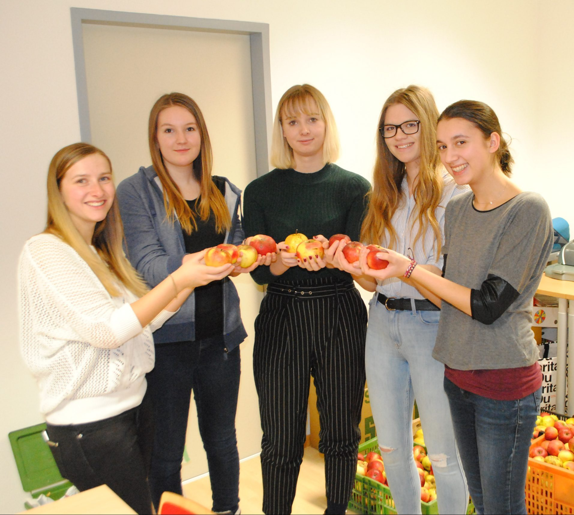 Vier actionPoolerin stehen mit der youngCaritas Referentin Simone mit je einem Apfel in der Hand zusammen. Sie wollen aus einigen Kisten Äpfel Apfelmus für das HelpMobil herstellen.