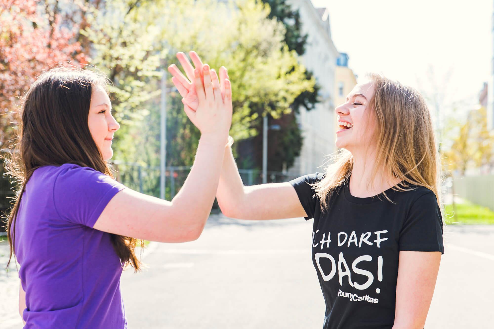 2 Jugendliche schlagen mit ihren Händen ein.