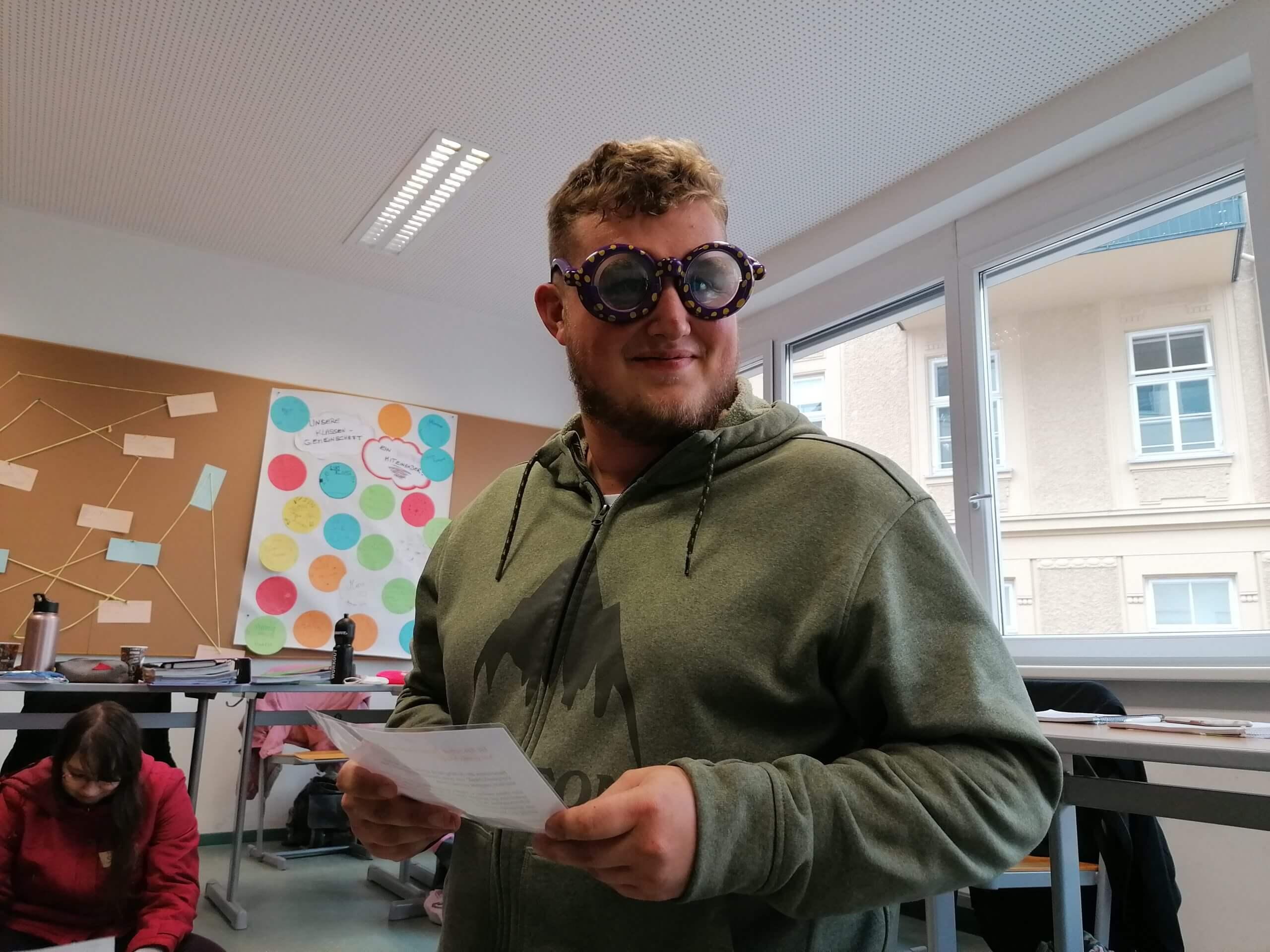Ein Jugendlicher hat eine Brille auf, die eine Sehbeeinträchtigung simulieren soll.